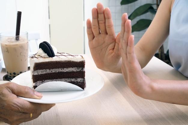 女性はケーキプレートとパールミルクティーを押します。体重を減らすためにデザートを食べるのをやめる。