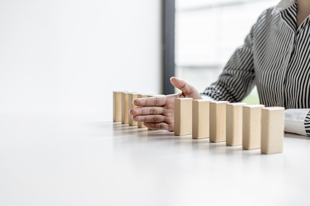 女性は、ドミノに配置された木製のブロックの間に手を置き、ビジネスをうまく運営し、問題を解決することに例えられます。リスクに関する経営管理の概念。