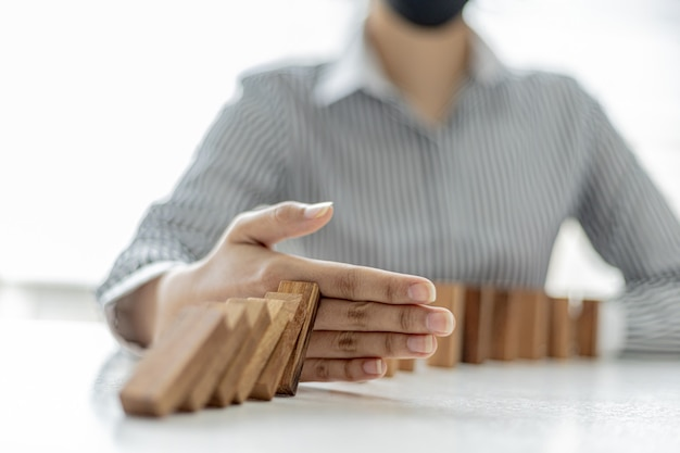 Women put their hands between wooden blocks, wooden blocks arranged in dominoes, likened to running a business well and solving problems. the concept of business management on risk.