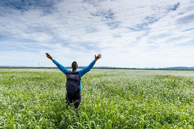 女性は彼女の手を上げて、美しい緑の牧草地にとどまります