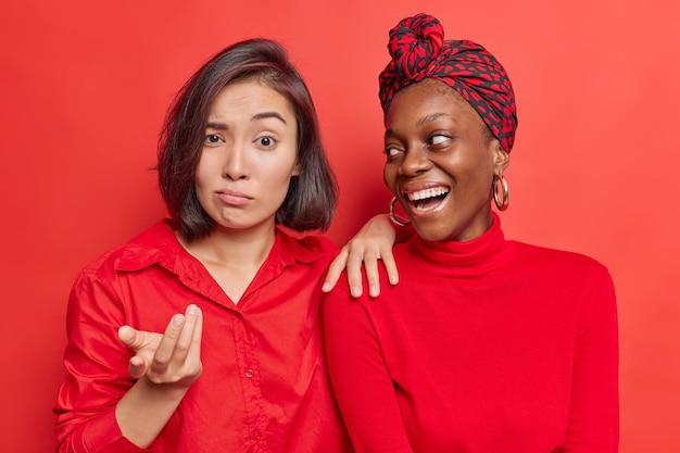 여성들은 무언가에 다르게 반응합니다. 밝은 빨간색으로 서로 가까이 서 있습니다.