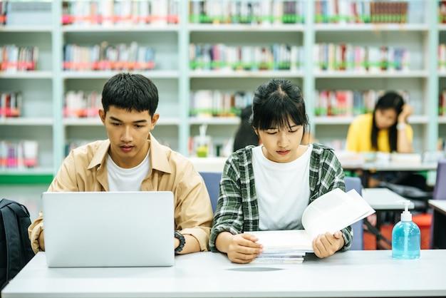 여자는 책을 읽고 남자는 노트북을 사용하여 도서관에서 책을 검색합니다.