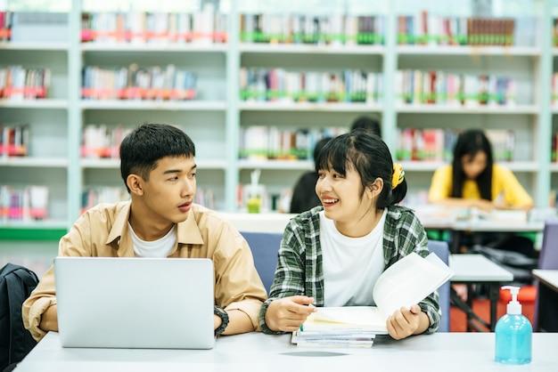 Le donne leggono libri e gli uomini usano i laptop per cercare libri nelle biblioteche.