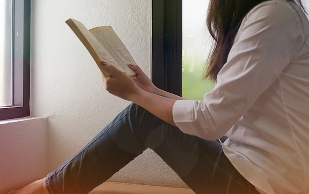 Women reading book and relaxing in her living room.selective focus