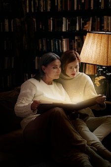 Women reading from a glowing book