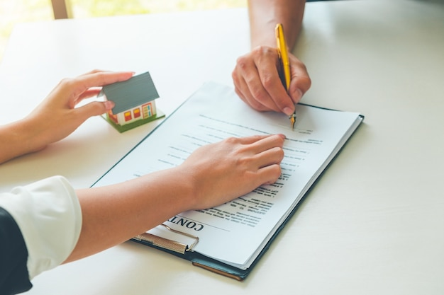 Women real estate agent showing where to sign on document for buy house contract