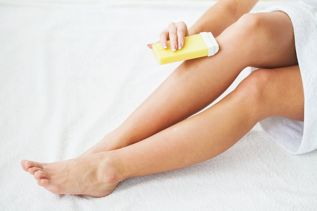 Women receive waxing for hair removal in her bathroom