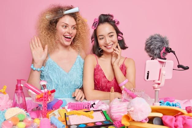 여성들은 추종자들과 블로그 대화를 위해 콘텐츠를 기록하고 화장품으로 가득 찬 테이블에 앉아 분홍색으로 격리된 스마트폰 카메라에 튜토리얼 비디오를 녹화합니다