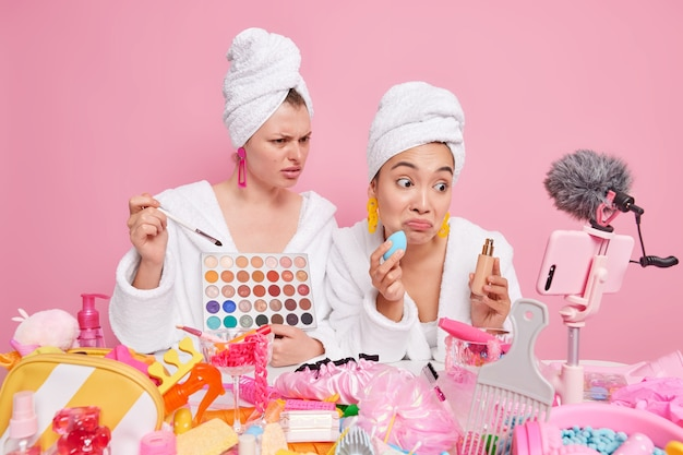 Women record tutorial video apply eye shadow and foundation on face dressed in domestic clothes sit at messy table with cosmetic products give detailed review. social media