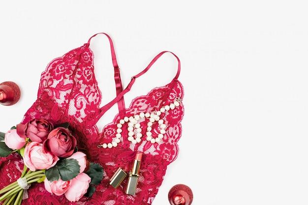 花と女性の赤いレースのランジェリーは、白い背景の上のアイテムを構成します。女性の日のはがき。