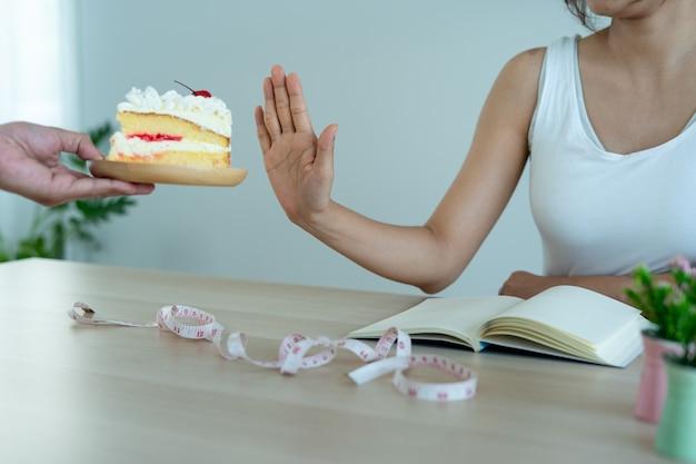 女性は友達のケーキを拒否します。女性の意図は、甘くて健康的な体重管理を食べることではありません。コンセプトダイエット