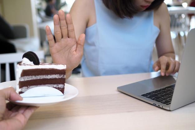 女性は、コンピューターでの作業中にケーキを食べることを拒否します。良い減量のために日中はうるさい食べ物を食べないでください。