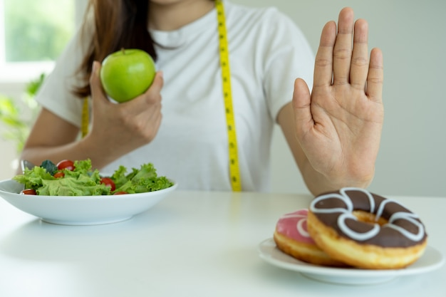 Women reject junk food or unhealthy foods such as doughnuts and choose healthy foods such as green apples and salads. concept of fasting and good health.
