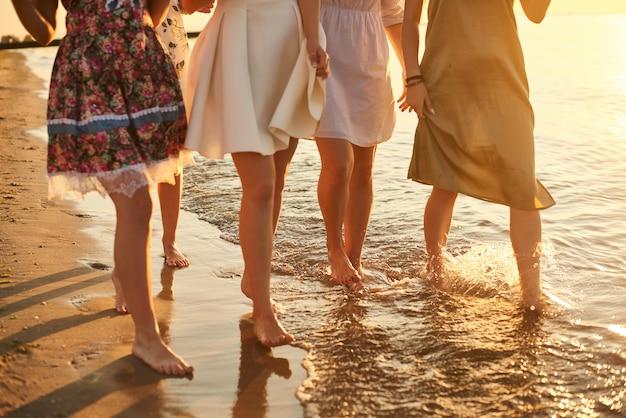 여성들은 리조트에서 휴식을 취합니다. 이른 아침 친구 바다에서 새벽을 만나
