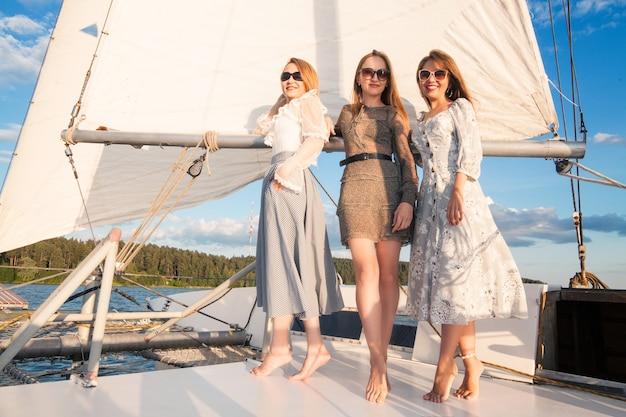 女性は海を背景に、ヨットでリラックスします。海でのコンセプト休暇。
