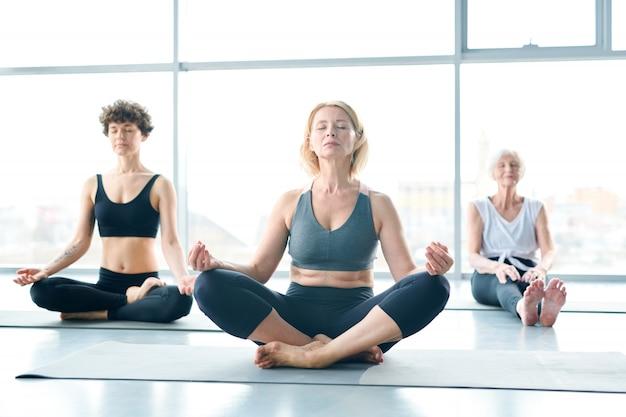 Women relaxing, doing yoga next to a large window