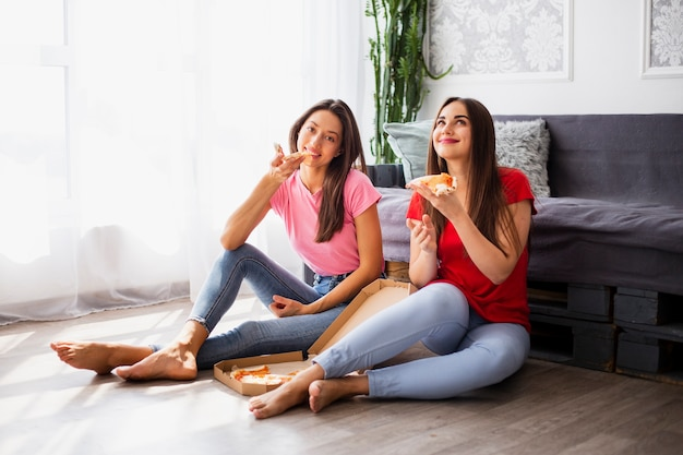 Women relaxing at home and eating popcorn