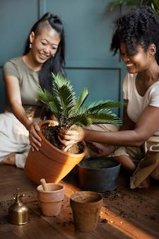 新しい通常の家で植物を植え替える女性