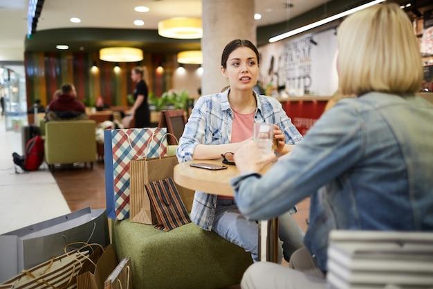 Женщины отдыхают в кафе после покупок
