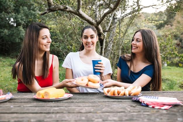 女性たちはピクニックに座っている