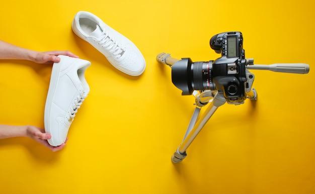 女性は三脚にカメラを備えた新しい白いスニーカーをレビューします。上面図。ミニマリズム