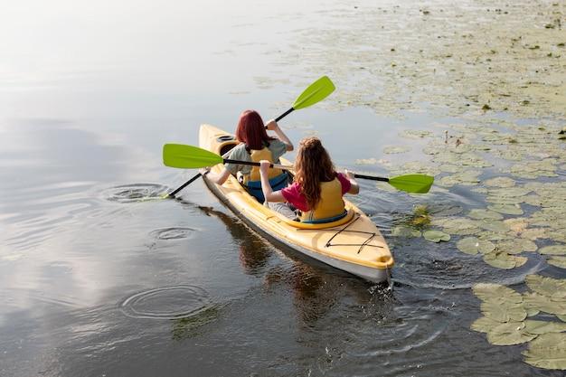 Women rowing in kayak on lake