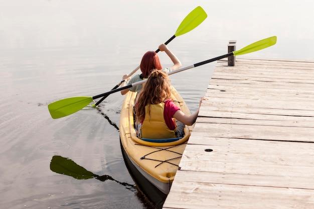 Women rowing kayak near dock