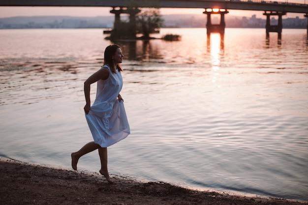 Женщины, бегущие на закате, очаровательная молодая женщина в белом летнем сарафане, бегающая босиком по ...