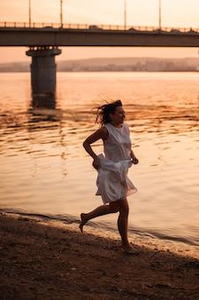 Женщины, бегущие на закате, очаровательная молодая женщина в белом летнем сарафане бегает босиком по ...
