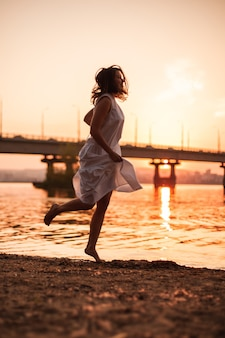 Женщины, бегущие на закате, образ жизни в полный рост, портрет кавказской женщины в длинном белом платье, бегут ...