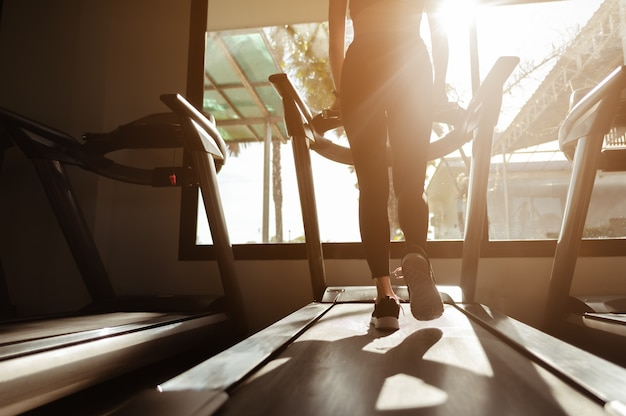 Women running in a gym on a treadmill fitness workout gym exercise lifestyle and healthy