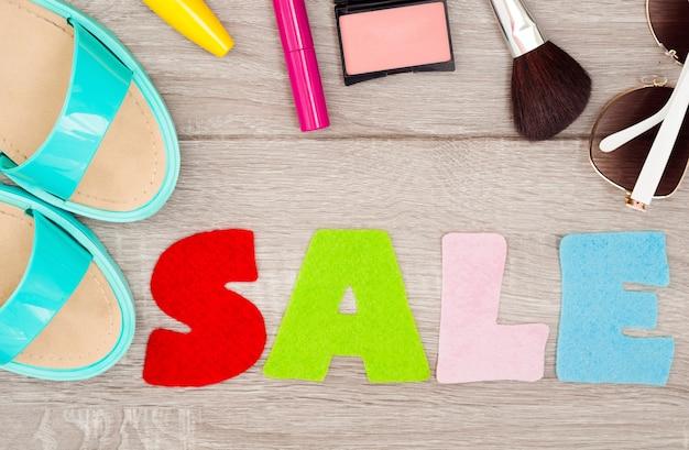 Женские аксессуары: летние сандалии, обувь, косметика, солнцезащитные очки. слово «продажа» из войлока на деревянном фоне.
