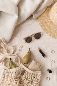 ベージュのブランケットに女性用アクセサリーとジュエリー。ストリングバッグ、麦わら帽子、サングラス、口紅、指輪、イヤリング、洋ナシ