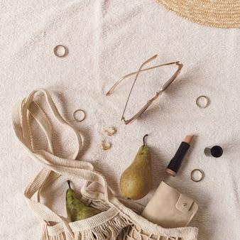 ベージュのブランケットに女性用アクセサリーとジュエリー。ストリングバッグ、麦わら帽子、サングラス、口紅、指輪、イヤリング、梨