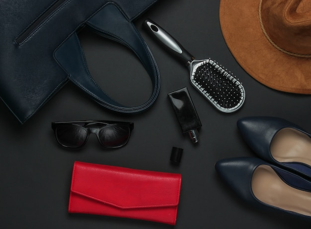 Women's accessories on a black background. hat, leather bag, comb, sunglasses, perfume bottle. top view