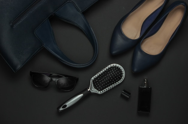 Women's accessories on a black background. high heel shoes, leather bag, comb, sunglasses, perfume bottle. top view