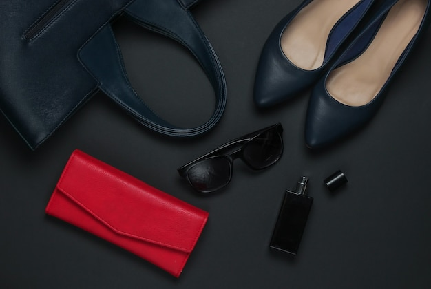 Women's accessories on a black background. high heel shoes, leather bag, purse, sunglasses, perfume bottle. top view