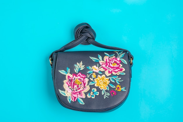 Women's accessories - blue handbag with flowers, trendy on blue surface flat lay