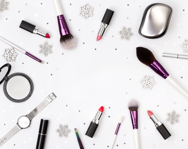 Women's accessories, cosmetics and makeup tools with christmas decorations on a white table