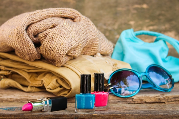 Women's accessories and cosmetics on old wooden background