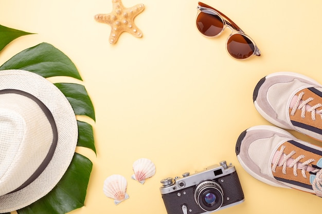 Women's accessories items on pastel yellow background, summer vacation concept.