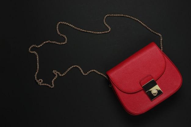 女性用アクセサリー。黒の背景に革の赤いバッグ。上面図