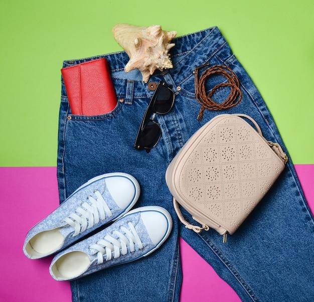 Женские аксессуары лежат на классических джинсах с завышенной талией. кроссовки, кошелек, сумка, пояс на розовом зеленом фоне. вид сверху. концепция путешествия.