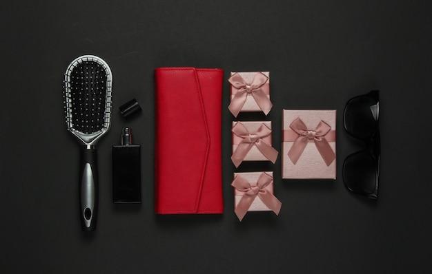黒の背景に女性のアクセサリー。くし、サングラス、香水瓶、財布、ギフトボックス。誕生日、母の日、クリスマス。上面図