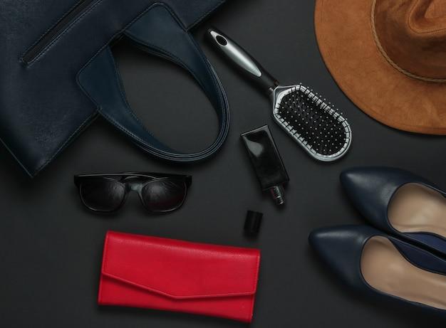 黒の背景に女性のアクセサリー。帽子、革製バッグ、くし、サングラス、香水瓶。上面図