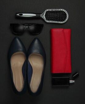 黒の背景に女性のアクセサリー。ハイヒールの靴、くし、サングラス、香水瓶、財布。上面図