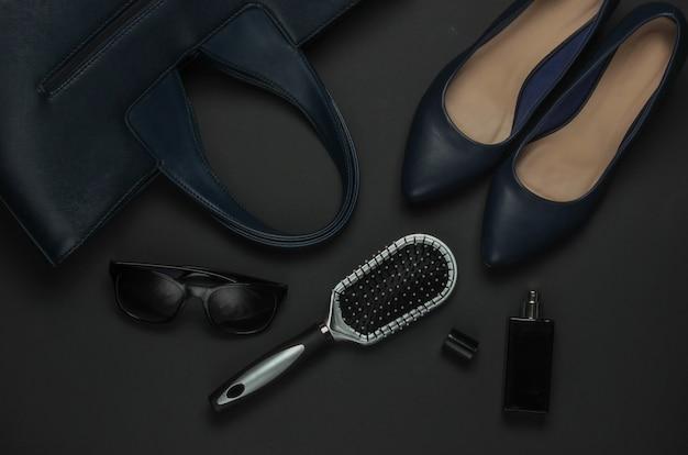 黒の背景に女性のアクセサリー。ハイヒールの靴、革のバッグ、くし、サングラス、香水瓶。上面図