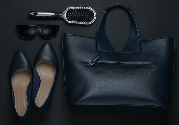 黒の背景に女性のアクセサリー。ハイヒールの靴、革のバッグ、くし、サングラス。上面図