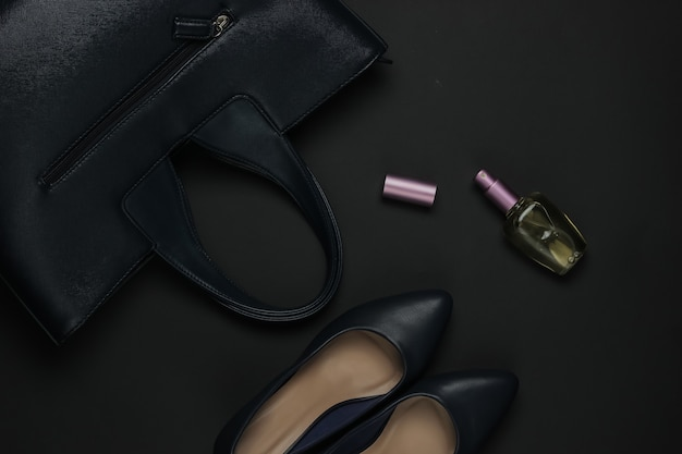 黒の背景に女性のアクセサリー。ハイヒールの靴、革のバッグ、香水瓶。上面図