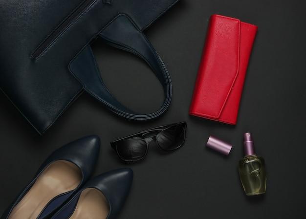 黒の背景に女性のアクセサリー。ハイヒールの靴、革のバッグ、財布、サングラス、香水瓶。上面図